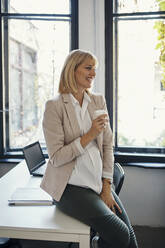 Pregnant businesswoman having a coffee break in office - ZEDF02787