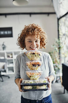 Portrait of smiling businesswoman holding stack of takeaway food in office - ZEDF02793