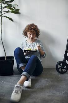 Businesswoman sitting on the floor in office having lunch break - ZEDF02799