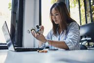 Businesswoman holding model car at desk in office - ZEDF02802
