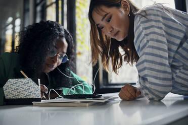 Two businesswomen sharing smartphone and earphones in office - ZEDF02808