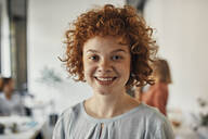 Portrait of a smiling redheaded businesswoman in office - ZEDF02820