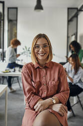 Portrait of a confident businesswoman in office with colleagues in background - ZEDF02826