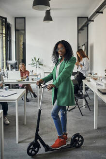 Portrait of a businesswoman with kick scooter in office - ZEDF02829
