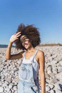 Portrait of young woman on empty beach, raising arm - AFVF04304