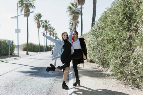 Two female friends having fun on the street - ERRF02195