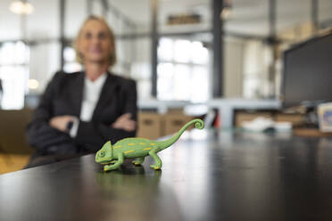 Mature businesswoman with chameleon figurine on desk in office - GUSF02700