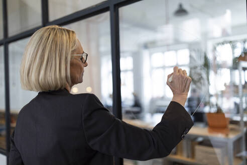 Mature businesswoman drawing on glass pane in office - GUSF02703