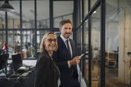 Smiling businessman and businesswoman standing at drawing on glass pane in office - GUSF02706