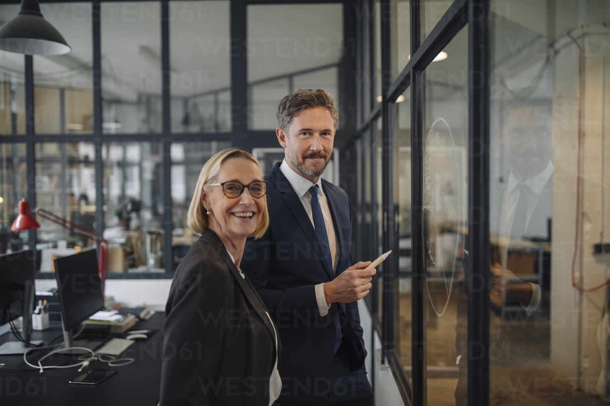 Smiling businessman and businesswoman standing at drawing on glass pane in office - GUSF02706 - Gustafsson/Westend61