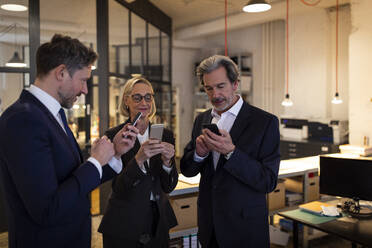 Business people using smartphones in office - GUSF02715