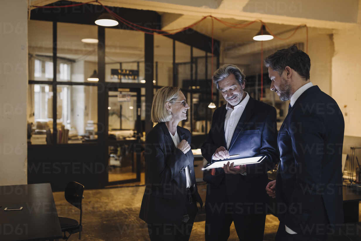 Business people with shining tablet talking in office - GUSF02718 - Gustafsson/Westend61