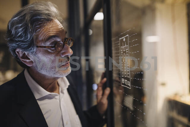 Senior businessman looking at drawing on glass pane in office - GUSF02751 - Gustafsson/Westend61