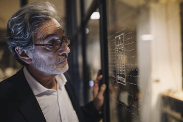 Senior businessman looking at drawing on glass pane in office - GUSF02751