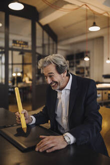 Silly senior businessman with giant pencil at desk in office - GUSF02772