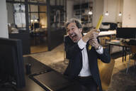 Angry senior businessman with giant pencil at desk in office - GUSF02775