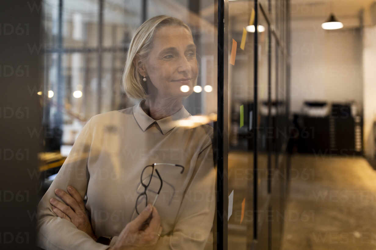 Mature businesswoman looking at adhesive notes on glass pane in office - GUSF02790 - Gustafsson/Westend61