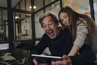 Happy casual senior buisinessman and girl using tablet in office - GUSF02868