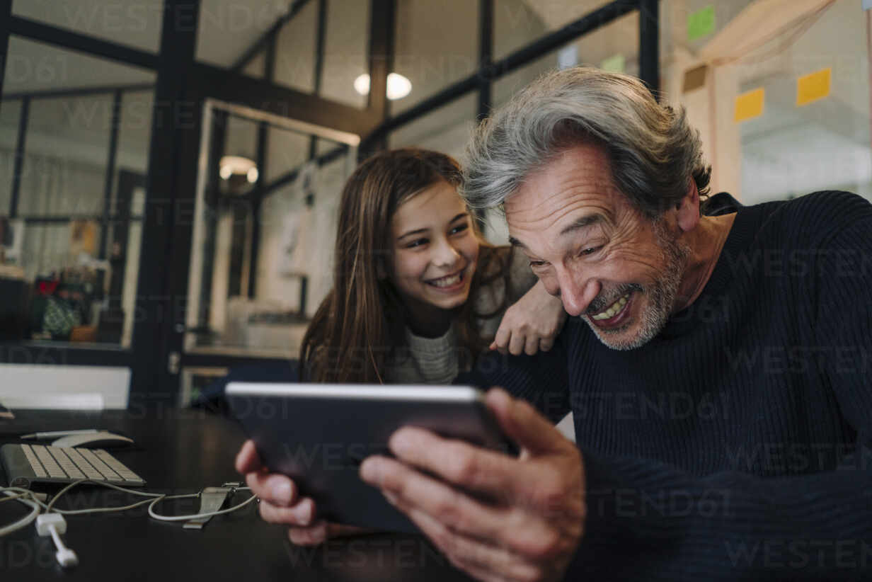 Happy casual senior buisinessman and girl using tablet in office - GUSF02871 - Gustafsson/Westend61