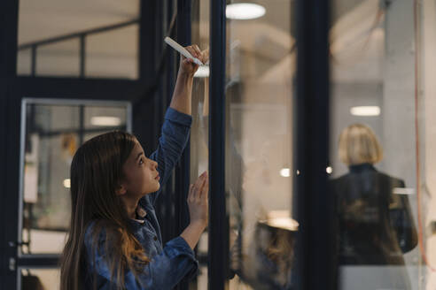 Girl drawing on glass pane in office - GUSF02877