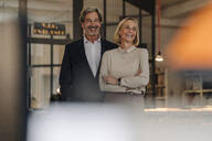 Portait of smiling businessman and businesswoman in office - GUSF02904
