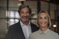 Portait of smiling businessman and businesswoman in office - GUSF02907