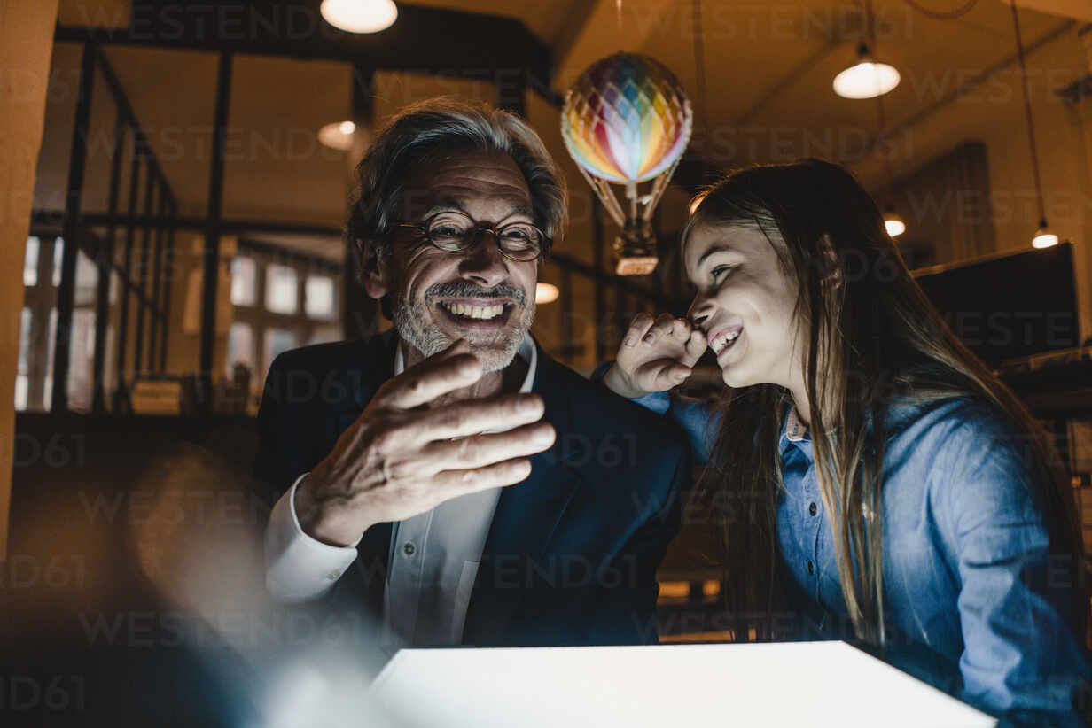 Happy senior buisinessman and girl with hot-air balloon and shining tablet in office - GUSF02910 - Gustafsson/Westend61