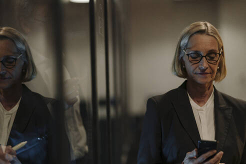 Mature businesswoman using smartphone in officereflected in glass pane - GUSF02919