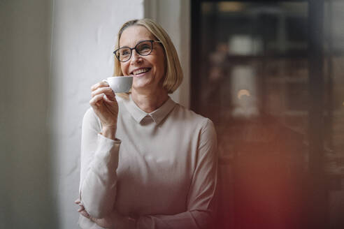 Smiling mature businesswoman having a coffee break at the window in office - GUSF02928