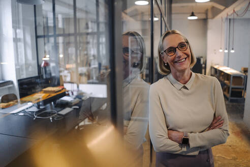 Portrait of smiling mature businesswoman leaning against glass pane in office - GUSF02937