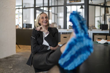 Laughing mature businesswoman with feet on desk wearing cleansing slippers in office - GUSF02940