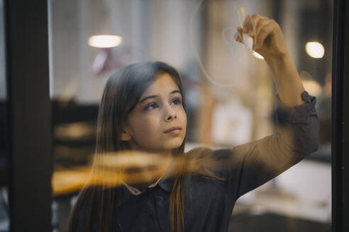 Girl drawing on glass pane in office - GUSF02943