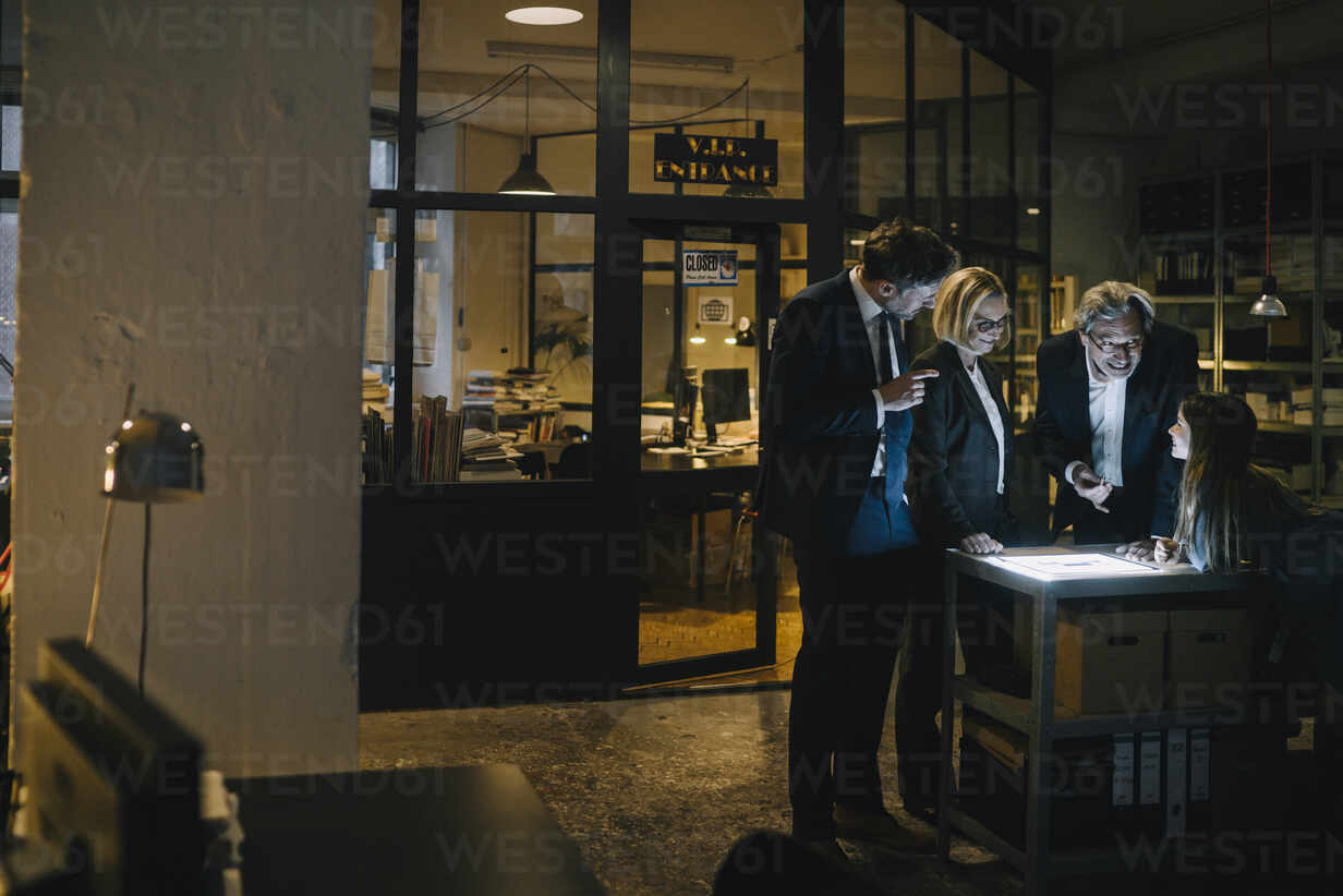 Business people and girl looking at shining tablet in office - GUSF02949 - Gustafsson/Westend61