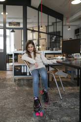 Girl with roller skates sitting at desk in office wobbling with chair - GUSF02964