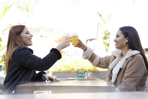 Two female friends clinking beer glasses outdoors at a cafe - ERRF02201
