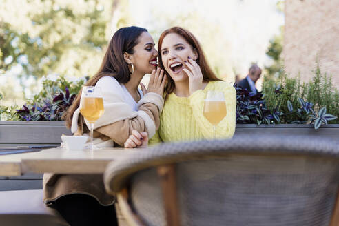 Two female friends whispering outdoors at a coffee shop - ERRF02204