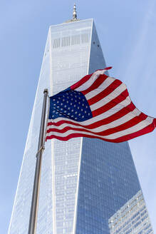 USA, New York, New York City, Low angle view of One World Trade Center and American flag - CJMF00175