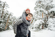 Portrait of happy young man giving his girlfriend a piggyback ride in winter forest - OCMF00927