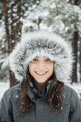Portrait of happy young woman in winter forest by snowfall - OCMF00930