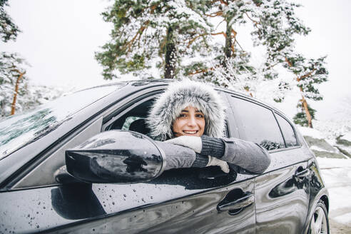 Portrait of smiling young woman leaning out of car window in winter forest - OCMF00933