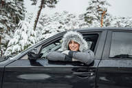 Portrait of smiling young woman leaning out of car window in winter forest - OCMF00936