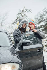 Laughing young couple with car in winter forest - OCMF00939