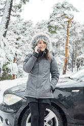 Portrait of happy young woman on the phone leaning at parked car in winter forest - OCMF00942