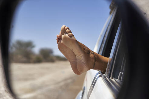 Woman with feet out of the car's window. Khwai, Botswana. - VEGF00857