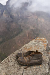 Pair of vintage boots on the top of a hill, Blyde River Canyon, South Africa - VEGF00872