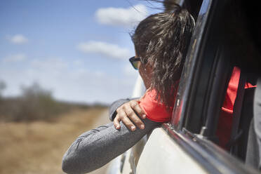 Woman admiring the landscape with the head out of the car window, Kruger National Park, South Africa - VEGF00875