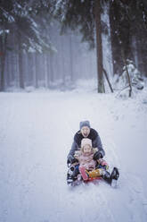Portrait of mature woman sledging together with her daughter - PSIF00337