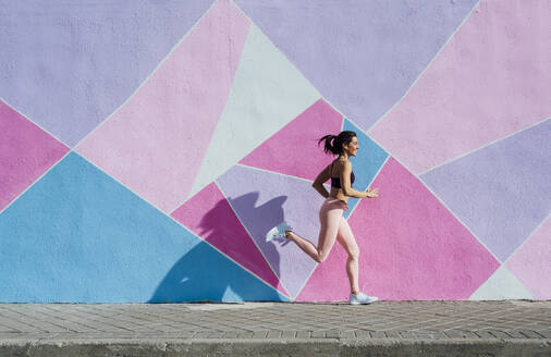 Mature woman running in front of a colorful wall - JCMF00304