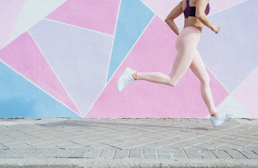 Woman running in the city in front of colorful wall - JCMF00310