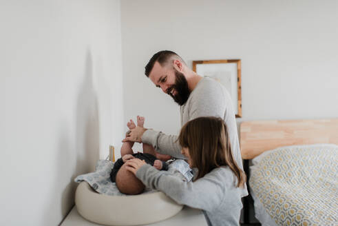 Young man and daughter changing baby son's diaper in bedroom, side view - ISF22977
